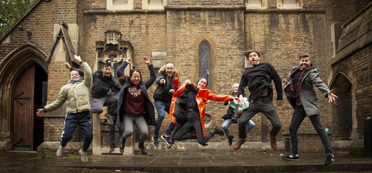 A group of happy young people, jumping in the air, outside Holy Cross Church on Cromer Street